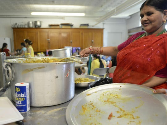 Rupa Poudyel prepares food to be served during the last of three days of a Puran celebration held in Burlington on Sunday.