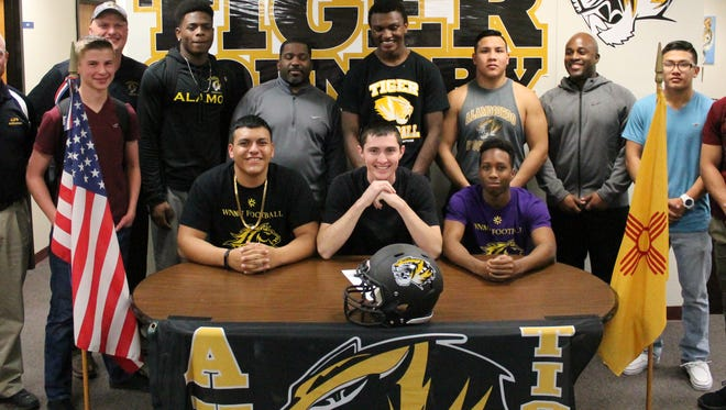 Scotti Velasco, front left, Kyle Hooper and Jalen Bateman posed for a picture alongside friends and coaches during National Signing Day Wednesday afternoon at Alamogordo High School. The trio inked with Western New Mexico University.