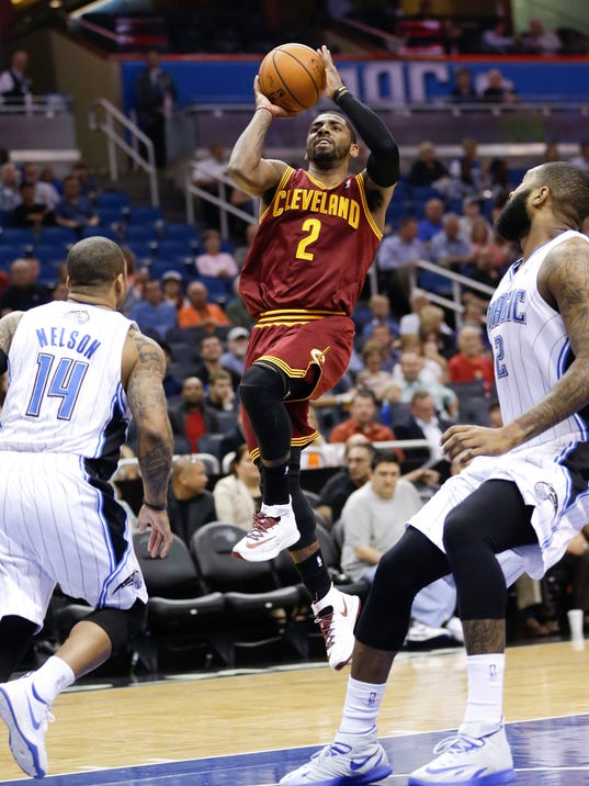 FILE - In this April 2, 2014 file photo, Cleveland Cavaliers' Kyrie Irving (2) makes a shot as he gets between Orlando Magic's Jameer Nelson (14) and Kyle O'Quinn, right, during the first half of an NBA basketball game in Orlando, Fla. Dogged by rumors that he has wanted out of Cleveland, Irving and Cavaliers owner Dan Gilbert tweeted early Tuesday morning, July 1, 2014,  that they have agreed to terms on a new five-year contract extension. (AP Photo/John Raoux, File)