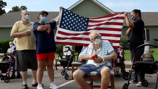 Thomas Arnold, from left, Sherry Woodard, and Annie Sayvongsa join WWII Navy Veteran centenary Tony Ulrich, seated, singing the National Anthem, Saturday, July 18, 2020, during Ulrich's 100th birthday parade passing in front of his home, Brookfield Assisted Living in Fianna Hills.