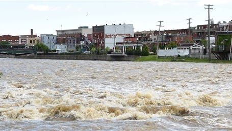 The River Raisin rages through Monroe on June 28, 2015.