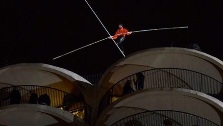 CORRECTS TO 19 DEGREES-Daredevil Nik Wallenda begins his tightrope walk uphill at a 19-degree angle from the Marina City west tower across the Chicago River to the top of the Leo Burnett Building in Chicago, Sunday, Nov. 2, 2014. (AP Photo/Paul Beaty)