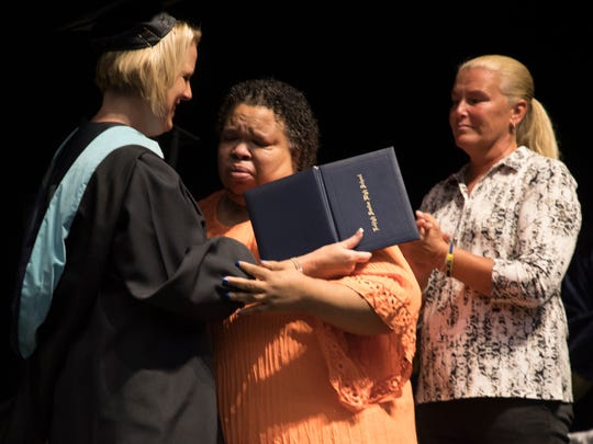 Stephanie White, the mother of Stef'an Strawder accepts his diploma from principal Jackie  at the Lehigh Senior High School graduation on May 21, 2017. Strawder was killed in the Club Blu shooting last year.