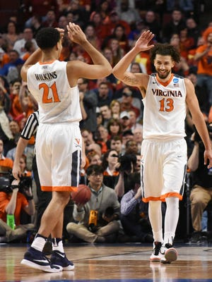Virginia Cavaliers forward Anthony Gill (13) and forward Isaiah Wilkins (21) celebrate after a basket against the Iowa State Cyclones during the second half in a semifinal game in the Midwest regional of the NCAA tournament at United Center.