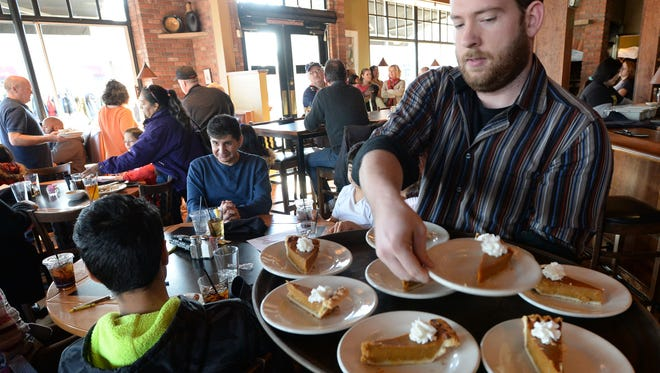 Chris Williams of Fort Collins serves pumpkin pie to a family at Austin's in Old Town on a past Thanksgiving day.