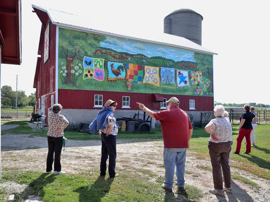 Larry Vance (center) points to something on his Elkhorn Township, WI, farm while talking with a tour group from Oak Park, IL. Vance and his wife, Judy, don't mind tourists visiting their farm.