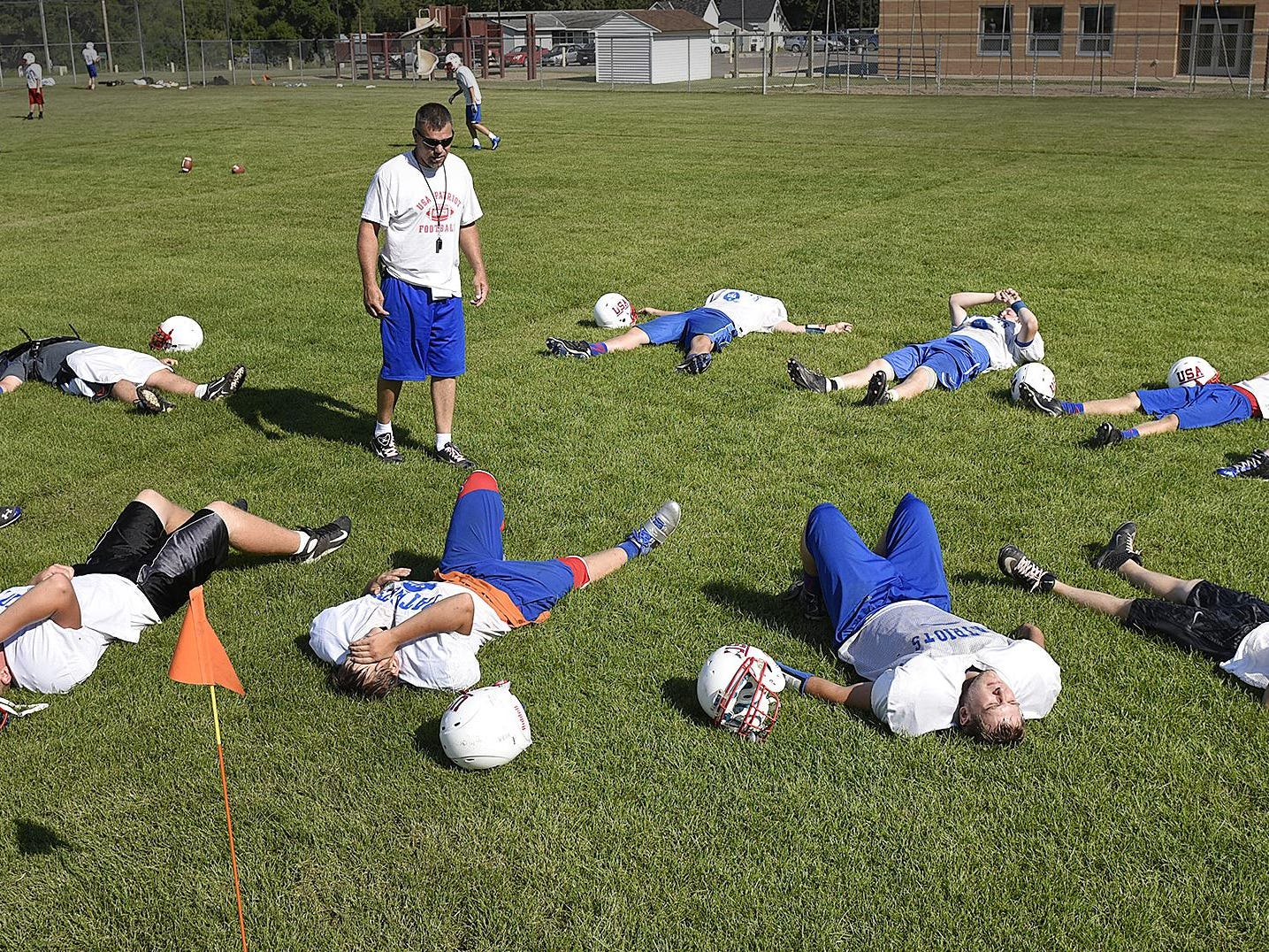 Coach Jay Loven talks to his players while giving them a break during practice Aug. 11 in Swanville.