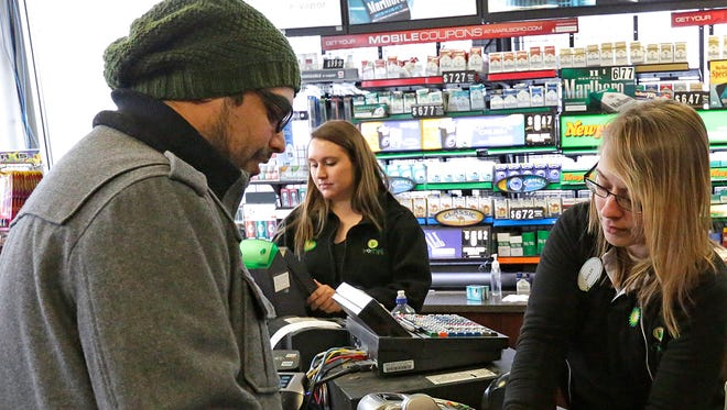 Hector Baez of Fond du Lac buys $100 worth of Powerball numbers at Korneli's on South Main Street in Fond du Lac on Wednesday afternoon. Baez was purchasing tickets as a group effort for employees at Wausau Equipment of Fond du Lac.