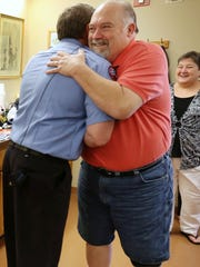 Norman Towell (right) hugs Dan McKinney, a firefighter with the Indianapolis Fire Department, at Station No. 43 on Saturday, April 11, 2015. Towell, 58, has had 30 surgeries since the day of the accident and lost his left leg after it became infected.