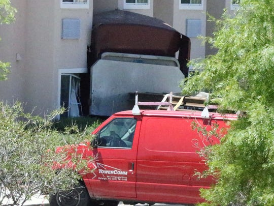 The cab of a tractor-trailer rig is seen Friday up against the wall of a hotel along South Desert Boulevard.