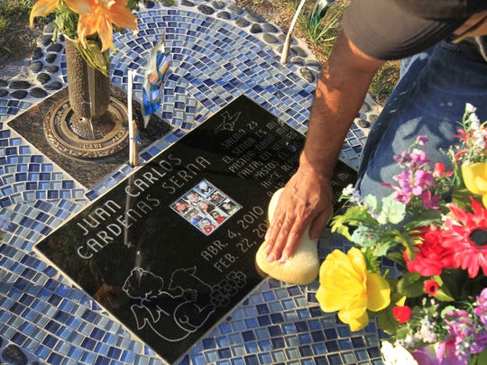 Juan Cardenas visits and cleans the gravesite of his son Juan Carlos Cardenas Serna, who was 22 months old when he died at a church day care in February 2012.