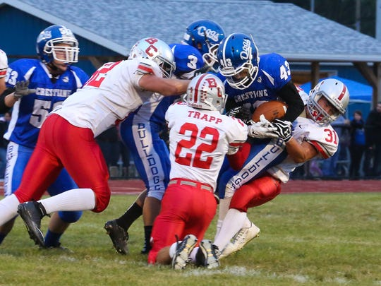 Buckeye Central players try to strip the ball from Sr. Michael Forwith Friday night during varsity football. - Timothy R. Russell