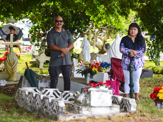 Tommy Iriarte attends the All Souls Day Mass near the grave of his mother, Maria Fausto Iriarte, along his wife, Doris Iriarte, at the Holy Cross Catholic Cemetery in Yona on Thursday, Nov. 2, 2017.