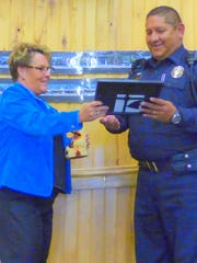 Village Manager Debi Lee presents a plaque to Ruidoso Police Officer Sal Beltran, public safety award recipient.