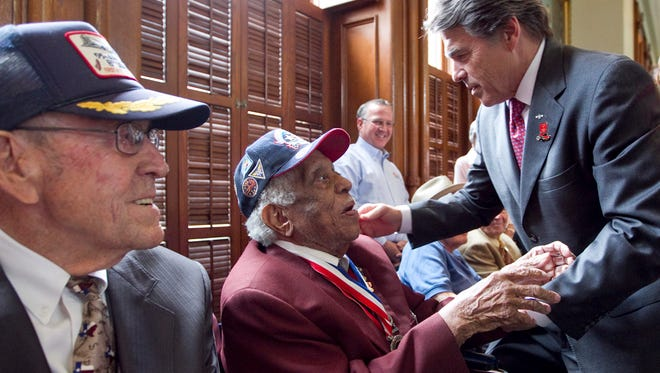 Gov. Rick Perry greets veteran Thomas Ellis as Perry's father Ray Perry smiles during a ceremony commemorating World War II veterans on the Senate floor on May 8, 2013.