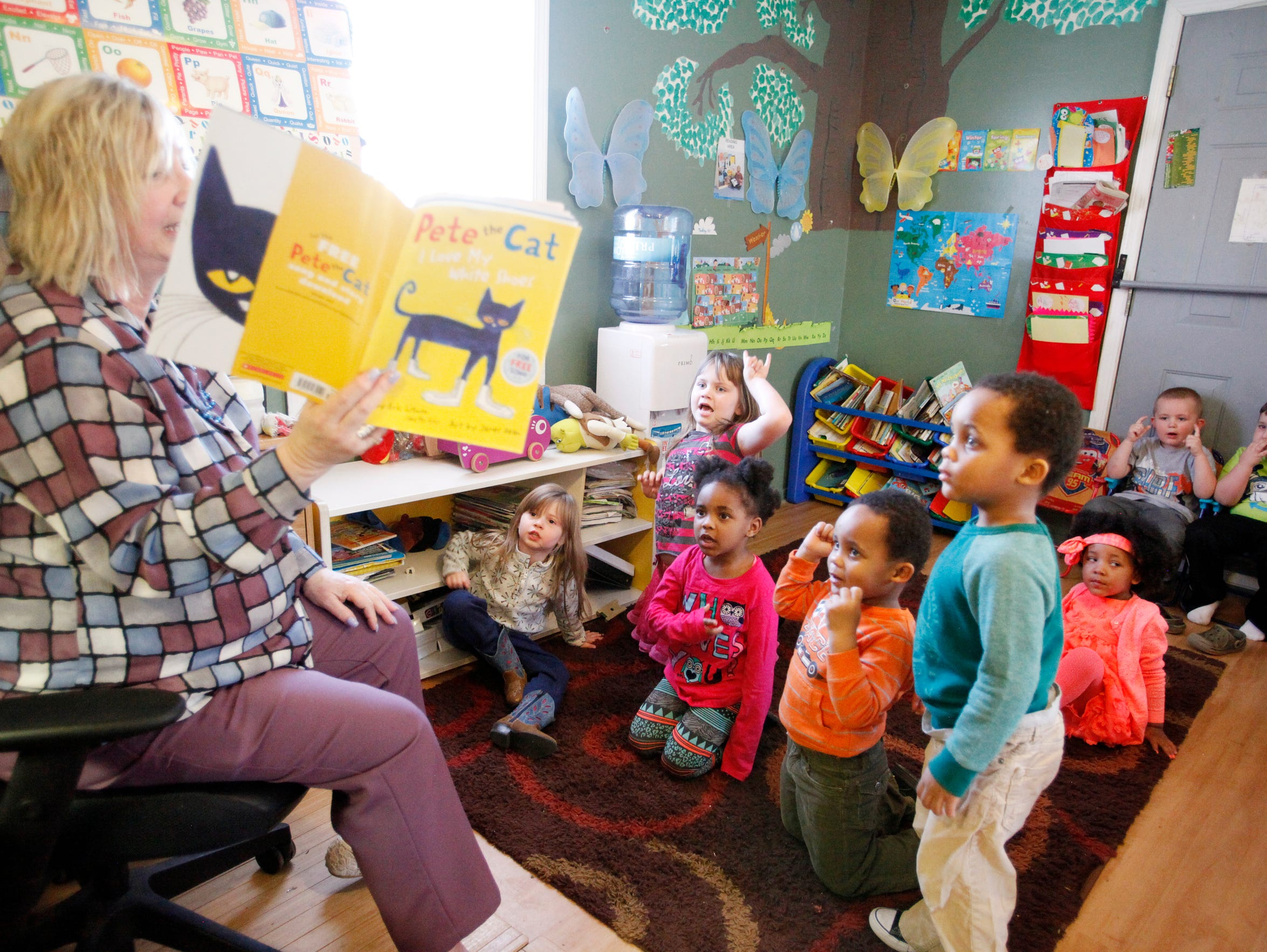 "Kathy Tolar reads ""Pete the Cat"" to children as they"