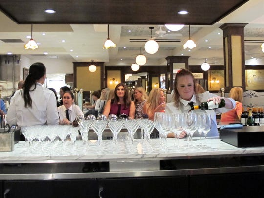 "Kristen Kincanon, a North Naples woman who won on ""Wheel of Fortune,"" is a bartender at The French Brasserie Rustique in Naples. She pours wine during a pre-opening event in January for the restaurant on Fifth Avenue South."