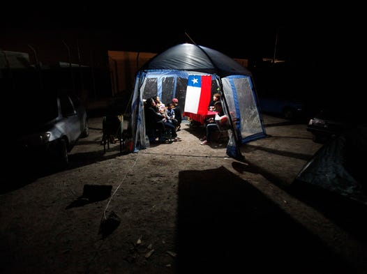 People take shelter in a tent decorated with a Chilean flag after evacuating their homes because of earthquakes in Alto Hospicio, Chile, on April 3, 2014. Coastal residents of Chile's far north spent a second sleepless night outside their homes as major aftershocks continued.