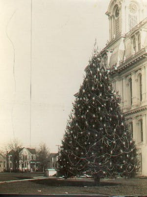 Salem's Christmas tree, boasted as the first live (uncut) community tree in the United States to be decorated with lights, is seen on the grounds of the Marion County Courthouse. Lit first in 1913, it was a Salem tradition until 1952, when it was uprooted.