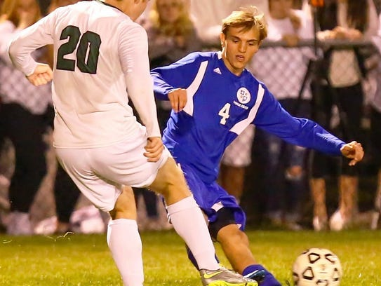 Catholic Central's Justin Savona (right) goes for the