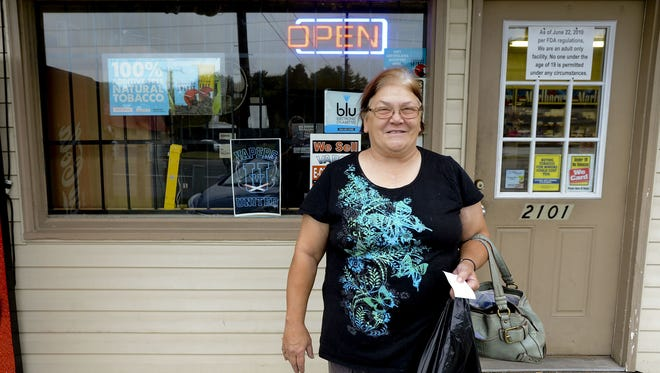 Susan Schmelter leaves the Discount Tobacco Outlet in of Decatur, with a carton of cigarettes. A 25-cent state tax increase on a pack of cigarettes went into effect Oct. 1.