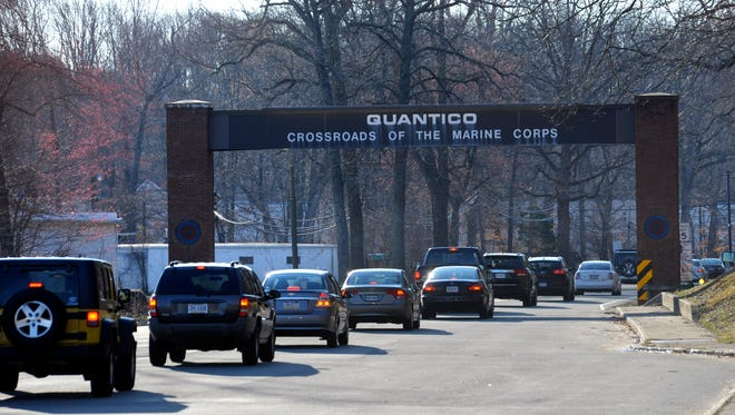 Cars pass under a sign at the entrance to the main gate at Quantico Marine Corps Base in Quantico, Va., Friday, March 22, 2013.