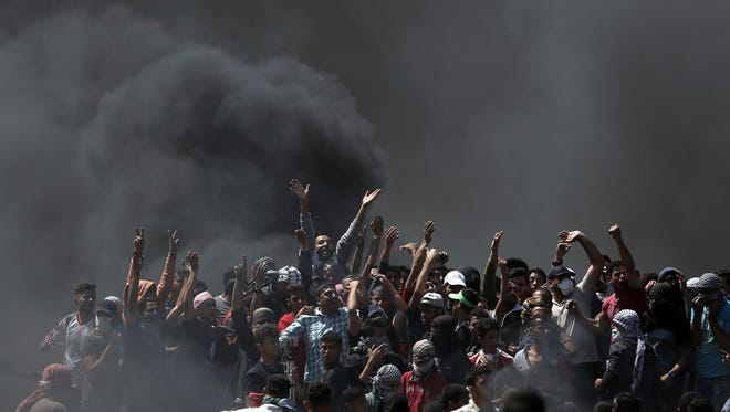 Palestinian protesters chant slogans as they burn tires during a protest on the Gaza Strip's border with Israel on Monday.