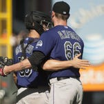 Oct 4, 2015; San Francisco, CA, USA; Colorado Rockies catcher Dustin Garneau (50) hugs relief pitcher John Axford (66) after defeating the San Francisco Giants 7-4 at AT&T Park. Mandatory Credit: Ed Szczepanski-USA TODAY Sports