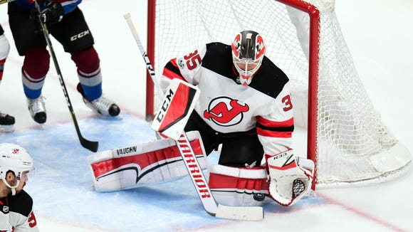 New Jersey Devils goalie Cory Schneider (35) makes a pad save in the second period against the Colorado Avalanche at the Pepsi Center.