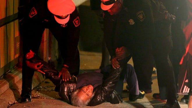 Patricia Carson collapses on the sidewalk in Lower Price Hill after learning her grandson was the victim of a fatal shooting the night of March 28, 2015