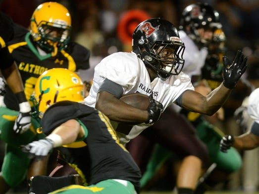 Navarre High School running back Michael Carter works his way through traffic Friday night in a game against the Catholic Crusaders.