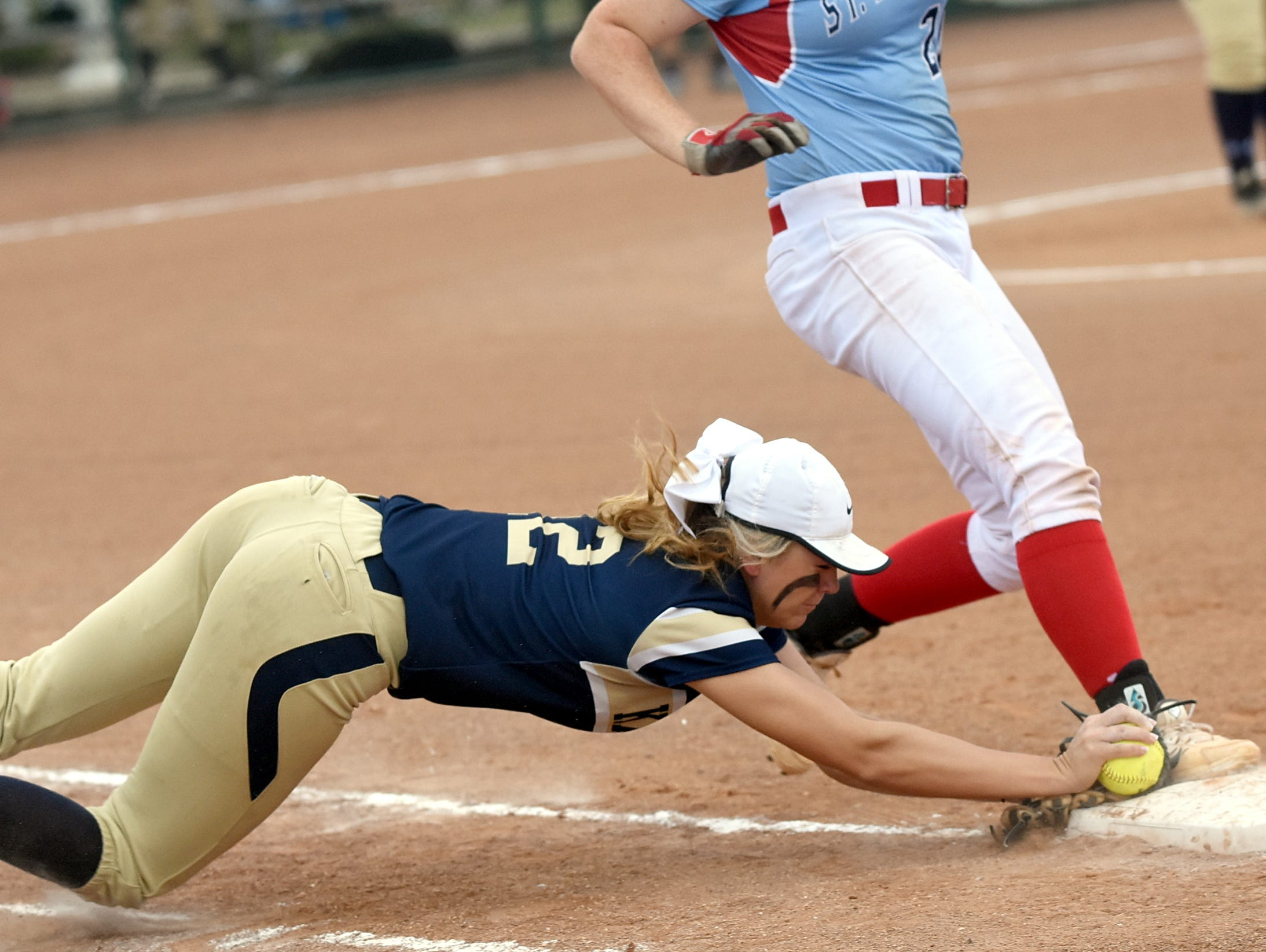 Pope John Paul II High senior first baseman Alley McDonald makes a diving tag of first base as St. Benedict junior Grace Sweat arrives during the first inning.