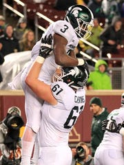 Michigan State running back L.J. Scott (3) celebrates his touchdown with tackle Cole Chewins (61) against Minnesota during the fourth quarter of MSU's 30-27 win on Saturday, Oct. 14, 2017, in Minneapolis.