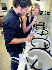 Philip Gravinese and Dr. Lauren Toth, co- organizers of Beneath the Waves film festival at Florida Tech's Gleason Performing Arts Center, culture larval peppermint shrimp in the FIT Aquaculture Laboratory.