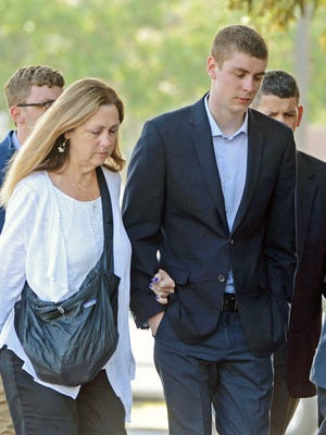 In this June 2, 2016 photo, Brock Turner, 20, right, makes his way into the Santa Clara Superior Courthouse in Palo Alto, Calif.