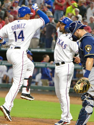 Elvis Andrus congratulates teammate Carlos Gomez after his three -run homer in the third inning.