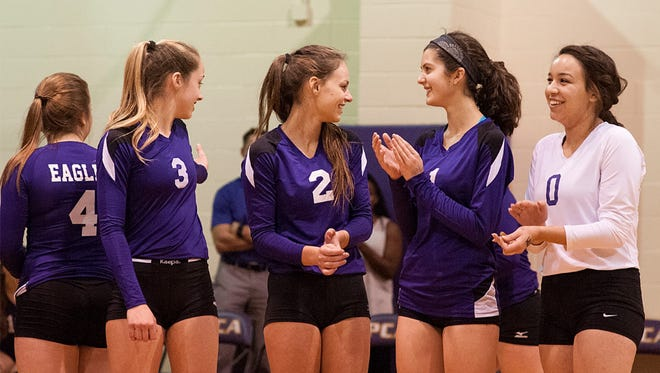 Plymouth Christian senior co-captains Olivia Mady (No. 1) and Divna Roi (No. 0) share a warm moment with teammates (from left) Abigail Pray, Grace Kellogg and Robin Albert during Friday's Class D district final.