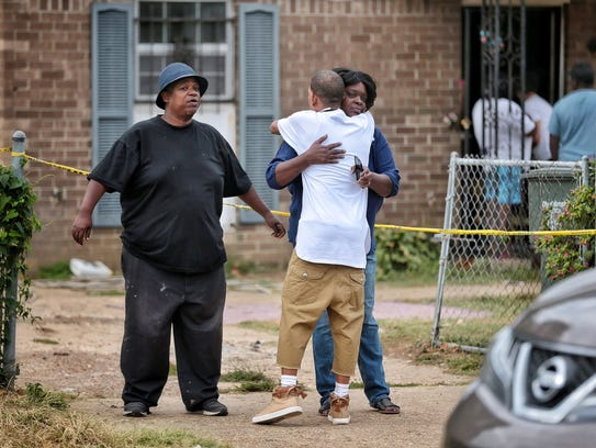Family members gather outside the scene of a fatal