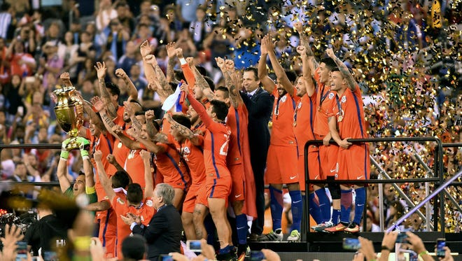 Chile's goalkeeper Claudio Bravo lifts the trophy after winning the Copa America Centenario final by defeating Argentina in the penalty shootout on June 26, 2016.