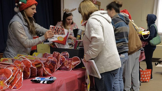 Parents sort through stockings at the Victor Christmas Stocking Program