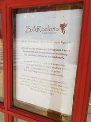 A sign on the door at BARcelona Tapas in Downtown Indianapolis announces the restaurant has closed but does not say why.