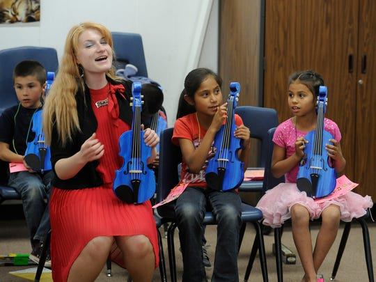 Music teachers Harmony Drumm, left, and Athena Saenz, not pictured, teach second graders Wednesday on identifying parts and correctly holding a violin, and the students will learn how to play during the HEARTstrings after school program at Woodville Elementary.