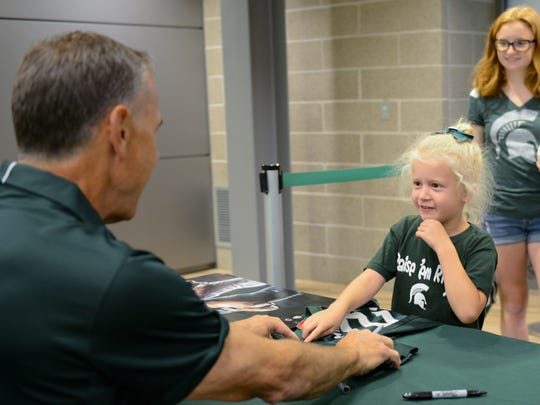 "Riley Orlowski, 6, of Mason, points out where she'd like MSU football coach Mark Dantonio to sign her Spartan football jersey during last year's ""Meet the Spartans"" event at Spartan Stadium."