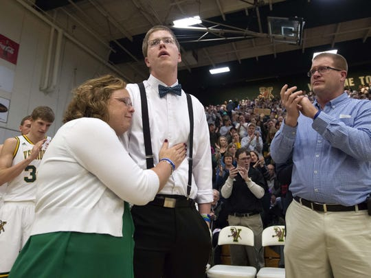 Josh Speidel gets a hug from his mother Lisa as his father Dave looks on before being introduced prior to the start of the University of Vermont's game against Stony Brook in January.
