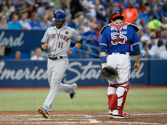Jul 4, 2018; Toronto, Ontario, CAN; New York Mets right fielder Jose Bautista (11) scores in the fifth inning on a single by left fielder Michael Conforto (30) as Toronto Blue Jays catcher Russell Martin (55) looks on at Rogers Centre. Mandatory Credit: