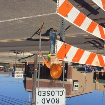 Worker installs Road Closed sign at Michigan and Fuller