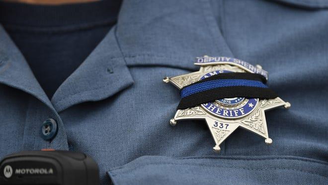 An Adams County Sheriff Deputy wears a black band across her badge after Sheriff's Deputy Heath Gumm was gunned down.