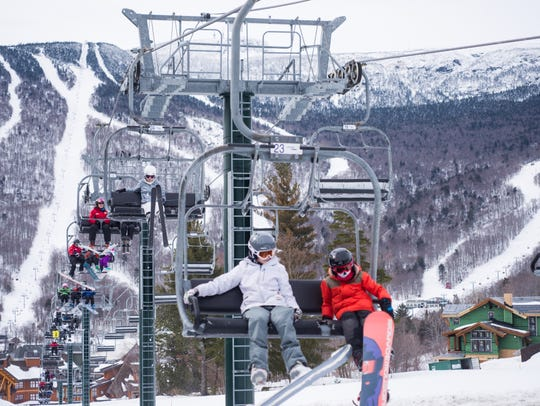 Skiers and snowboarders make their way up the mountain