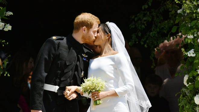 Britain's Prince Harry, Duke of Sussex kisses his wife Meghan, Duchess of Sussex as they leave from the West Door of St George's Chapel, Windsor Castle, in Windsor, on May 19, 2018 after their wedding ceremony. / AFP PHOTO / POOL / Ben BirchallBEN BIRCHALL/AFP/Getty Images