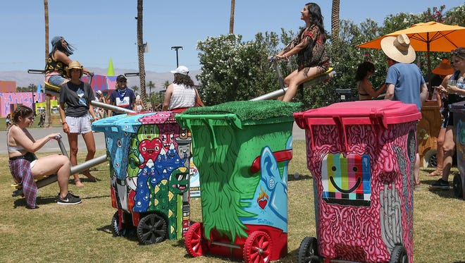 People generate power on a teeter totter near the Trashed recycling/art garbage bins at the Coachella Valley Music and Arts Festival. Efforts are being made to encourage recycling of discarded plastic water bottles and other waste left by attendees.